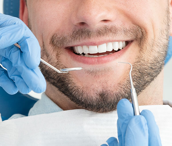 A closeup of a man's smile with two gloved hands holding a dental mirror and pick